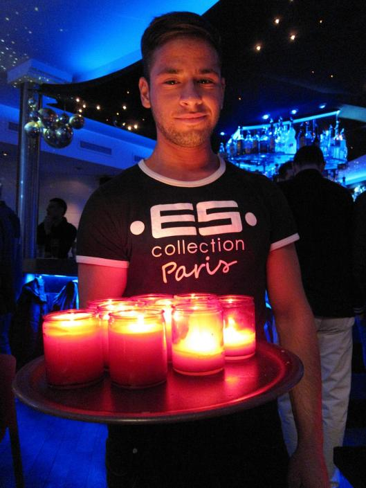 A barback at L'Open Café distributing candles.