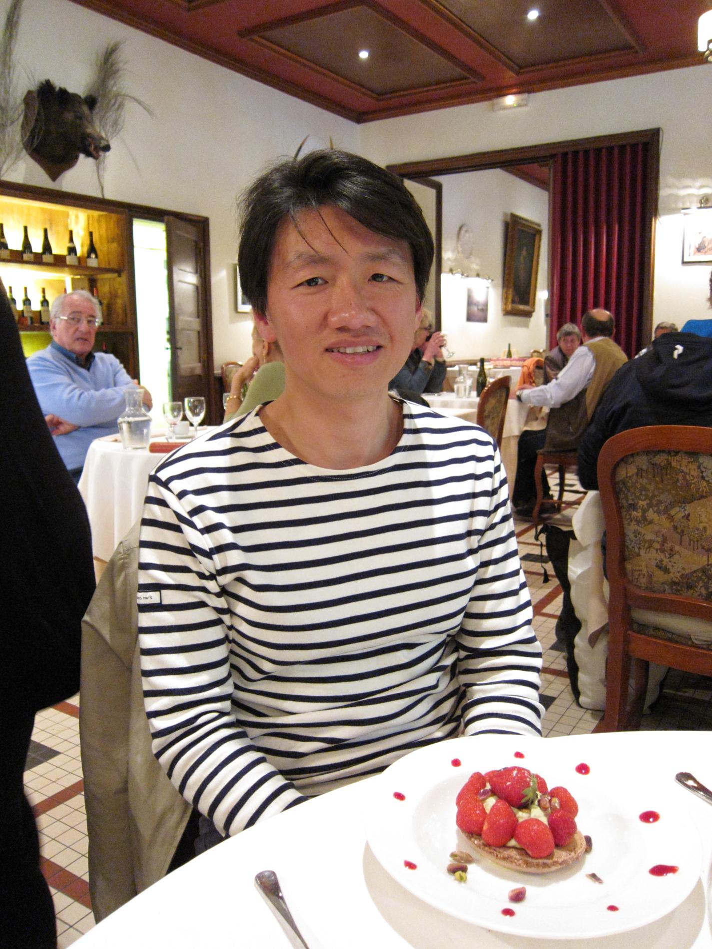 Zhizhong with his dessert at the Restaurant du Grand Saint Michel at Chambord, seemingly oblivious of the menacing sanglier looming behind him!