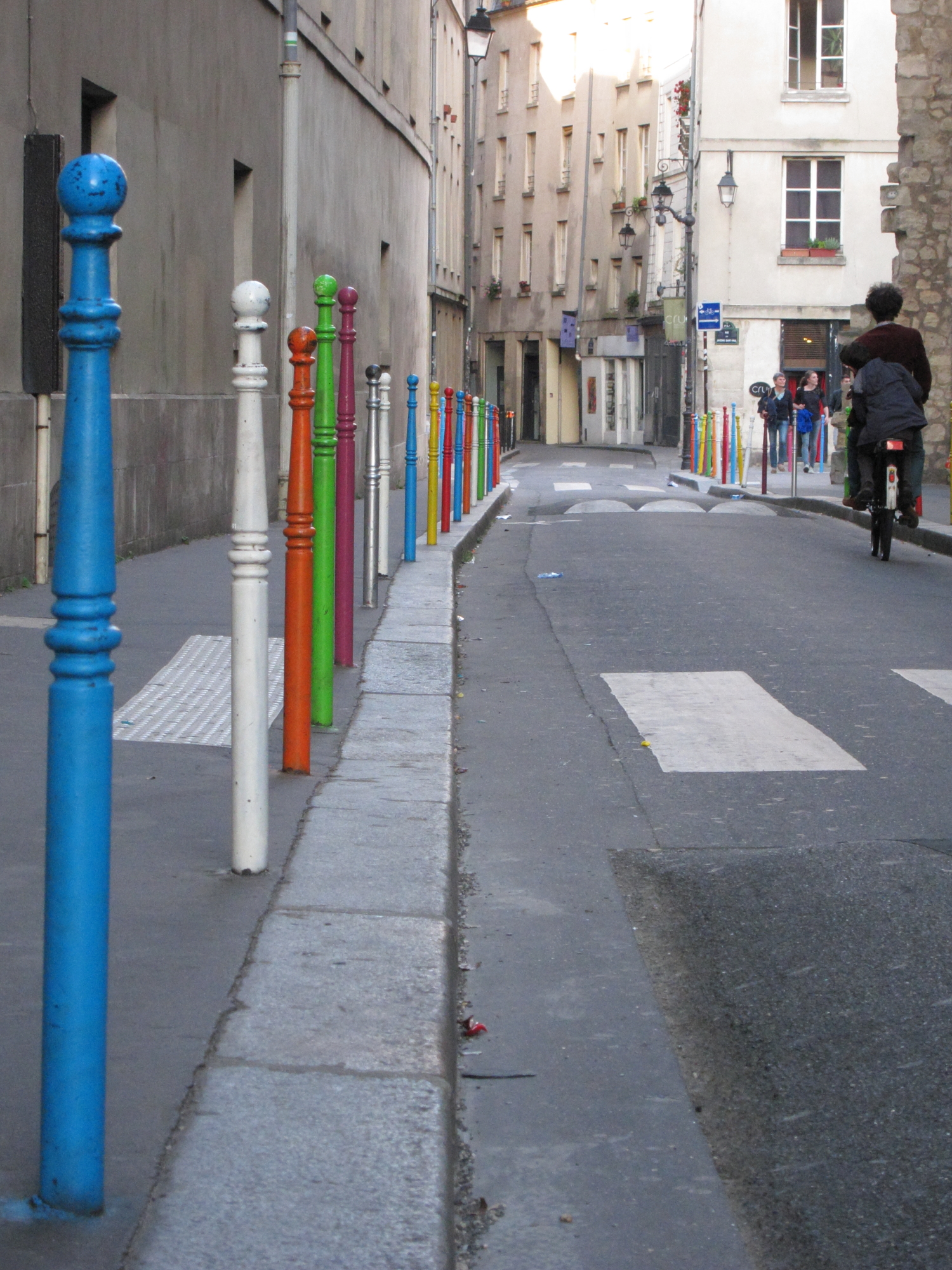 Festive pedestrian posts in Saint-Paul. The stonework at right is one of the last remnants of the 12th century city wall of Philippe-Auguste.
