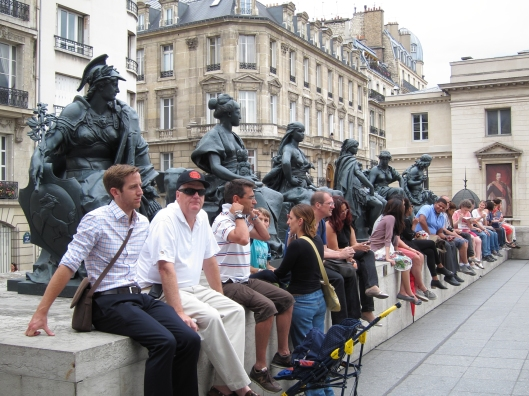 Tourists unconsciously echoing statues on the plaza of the Musee d'Orsay.