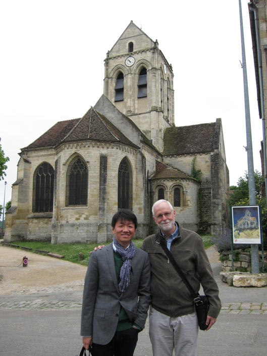 Zhizhong and me with the church at Auvers-sur-Oise and a sign showing van Gogh's painting of the same scene.