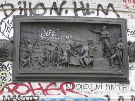 "Bas relief of a key meeting during the French Revolution, updated to say. ""Cops stay out of our lives!"""