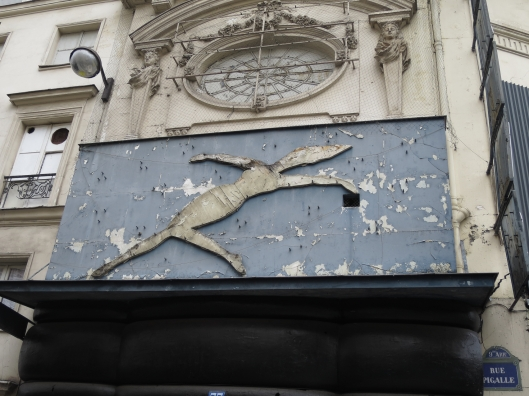 Formerly beautiful woman on sign on formerly beautiful building, rue Pigalle